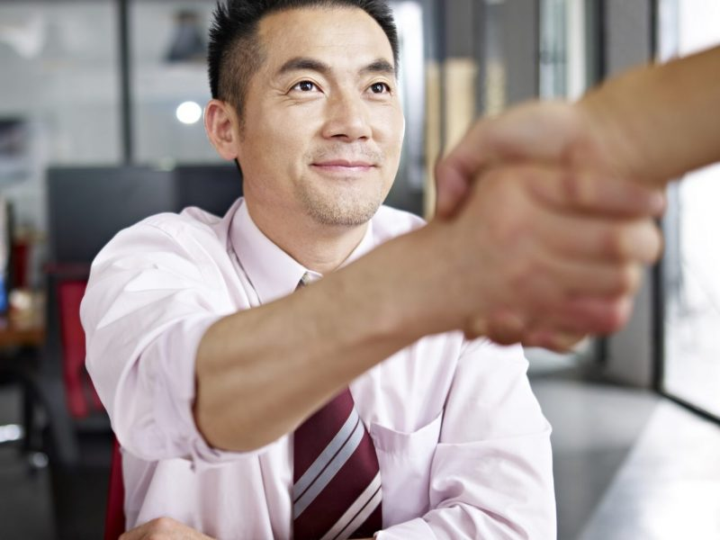 a man sitting at a desk in a white collard shirt and tie shaking the hand of a person off camera